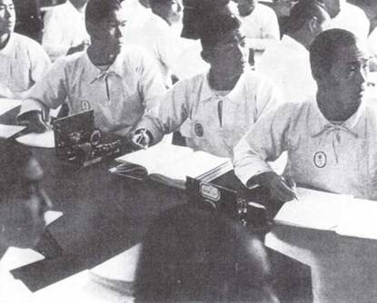 Курсанты внимательно слушают лекцию. Обратите внимание на небольшие овальные нашивки с именем на рабочей форме.(Эдвард М. Йонг)