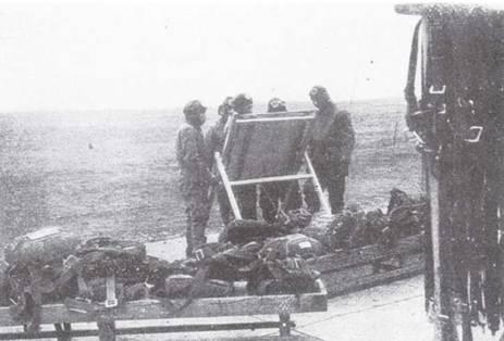Пилоты собрались у доски с ежедневным расписанием попетое. Парашюты разложены на подставках, справа на вешалке — ремни обвязки.