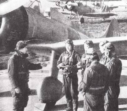 Старший пилот объясняет преимущества палубного истребителя Тип 96 «Кансен» группе выпускников летного училища, только что прибывших в часть.