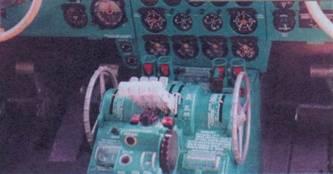 Центральный пульт в кабине летчиков: рычаги управления двигателями, штурвальчики триммера руля высоты, пульт управления автопилота, кнопки флюгирования двигателей и др.