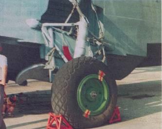 Левое колесо основной опоры шасси. Через три отверстия происходит охлаждение тормозов, метки служат для контроля за проворачиваЙ* нием шины на диске