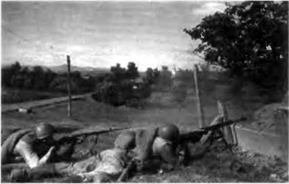 Расчет противотанкового ружья ведет огонь по противнику