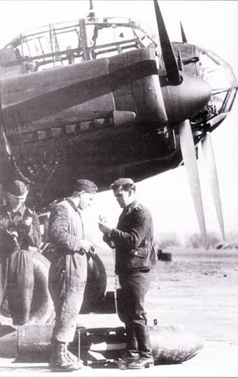 Оружейники подвешивают ни Ju-88A-I из KG-1 бомбы SC-250. Правой бомба снабжена картонным устройством, которое при свободном падении в воздухе генерирует акустический сигнал от набегающего потока воздуха. Такие звуки сеяли панику среди пехоты противника.