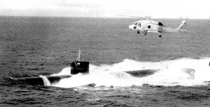 Вертолет Сикорский SH-60F «Оушен Хок» завис над атомоходом SSN-718 «Гонолулу» в Тихом океане. Вертолет принадлежит эскадрилье HS-4, геликоптер базировался на авианосце «Китти Хок». Лодка и вертолет отрабатывают совместные действии по поиску и уничтожению вражеских субмарин в водах гавайского архипелага.