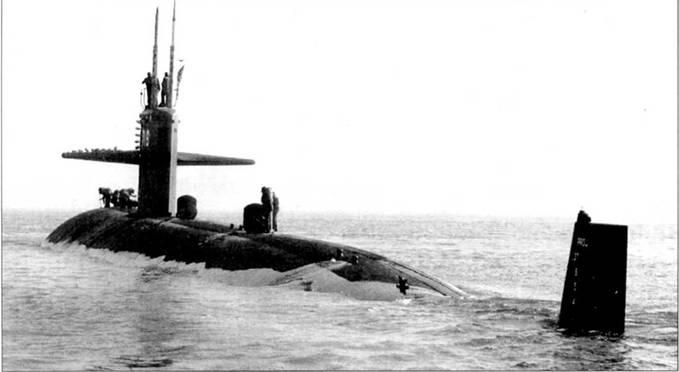 SSN-716 «Солт Лейк Сити» идет вниз по Джэмсовой реке, Вирджиния, 1984 г. Команда готовит субмарину к погружению. Необычный девайс на вертикальном оперении является навигационным огнем.