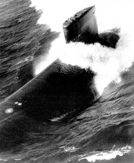 SSN-755 «Майами» на поверхности, номер на рубке закрашен. Белые круги на корпусе – аварийные буи. Более светлая панель в верхней части рубки – антенна минопоисковой ГАС. Атомоход «Майми» вошел в строй ВМС США в 1989 г.