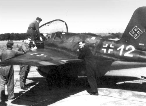 На этой пропагандистской фотографии, пилоты Me 163B готовятся к вылету. Фельдфебель Зигфрид Шуберт разговаривает по телефону (второй слева). Полевой телефон лежит на крыле и используется для поддержания связи с пилотом и командным пунктом.