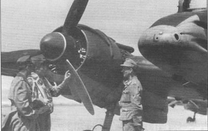 Курсант изучает правый двигатель Гном-Рон 14М самолета Hs-129B. Трехлопастные воздушные винты двигателей Хеншеля вращались в противоположные стороны (по направлению к продольной оси самолета) для компенсации гироскопического момента. Кончик кока воздушного винта окрашен в красный цвет, узкая белая полоса отделяет красную окраску передней части кока от черной задней части. Лопасти винта покрашены в черно-зеленый цвет (RLM70, FS34050), логотип фирмы Ратье, нанесенный на каждую лопасть, – белого цвета. Тесная кабина не позволяла разместить в ней все необходимые приборы, поэтому некоторые из них установить на внутренней поверхности мотогондолы ниже выхлопного патрубка.