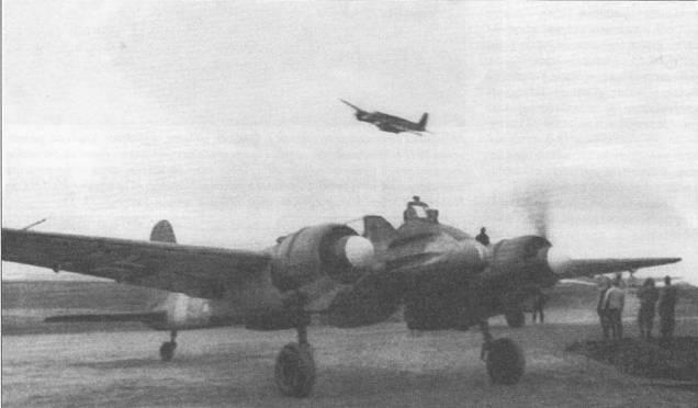 Хеншель Hs-129B-2 позднего выпуска выруливает на старт, штурмовик на заднем плане, наоборот, заходит на посадку. На самолетах модификации «В-2» (исключая машины раннего выпуска) отсутствовала мачта натяжной проволочной радиоантенны, выхлопные патрубки двигателей выполнялись более короткими, была изменена форма обтекателей воздушных фильтров, установленных под мотогондолами. На этом Hs-129B-2 под фюзеляжем смонтирована 30- мм автоматическая пушка МК-103.