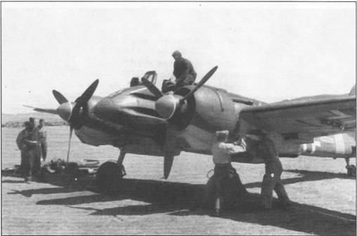 Механик помогает летчику занять место в кабине штурмовика Hs-129B- 2 перед боевым вылетом, аэродром в русской степи, лето 1942 г. Двое механиков пытаются запустить левый двигатель ручным инерционным стартером. Второй мотор также предстоит запускать ручным стартером.