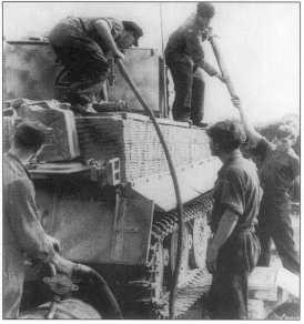 Pz.Kpfw.VI Ausf.E номер «214» (черного цвета с белой окантовкой) заправляют топливом. Западная Украина, июнь 1944 года.