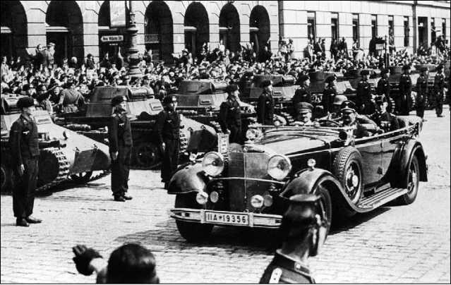 Гитлер проезжает в автомобиле мимо строя танков и их экипажей вновь сформированной танковой части. Судя по форме танкистов, этот снимок сделан после мая 1936 года.