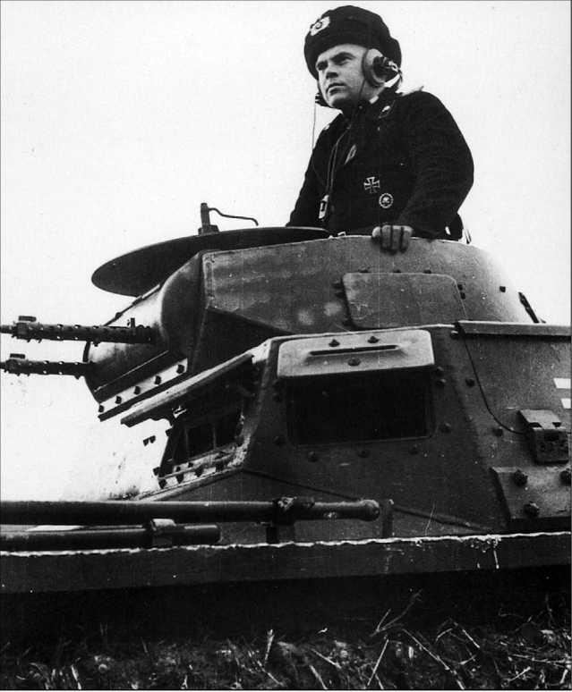 Pz.I Ausf.B и немецкий танкист крупным планом. Танки Pz. I разных модификаций легко идентифицировать по размещению ЗИПа и инструментов на надгусеничных полках. У этого танка на надгусеничной полке впереди слева размещены лопата и топор (их рукояти видны на снимке), но нет огнетушителя. Значит, это машина модификации «В», у которой огнетушитель располагался слева сзади.