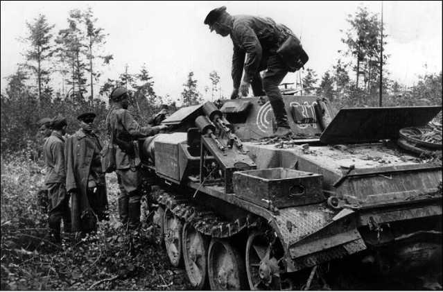 Бойцы и командиры Красной Армии осматривают захваченный огнеметный танк противника. Хорошо видна установка дымовых гранатометов на надгусеничной полке. Западный фронт, лето 1941 года.