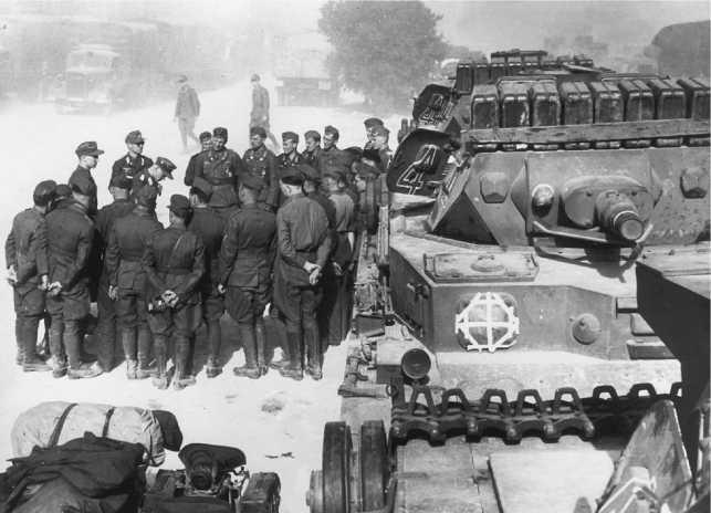 Только что прибывшее в Африку подразделение 5-й легкой дивизии Вермахта перед маршем. 1941 год. Обращают на себя внимание многочисленные канистры с бензином и водой на крыше башни этого Pz.IV Ausf.D, а также тщательно загерметизированные канал ствола пушки и амбразуры пулеметов и прицела, во избежание попадания в них пыли.