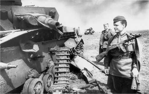 Командир артиллерийской батареи гвардии старший лейтенант Жихарев П.П. и старший сержант Дорохов осматривают разбитый немецкий танк Pz.IV. Юго-Западный фронт, 1942 год.