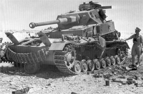 Английский офицер осматривает подбитый, сгоревший и частично разрушенный взрывом боекомплекта Panzer IV Special. Северная Африка, лето 1942 года.
