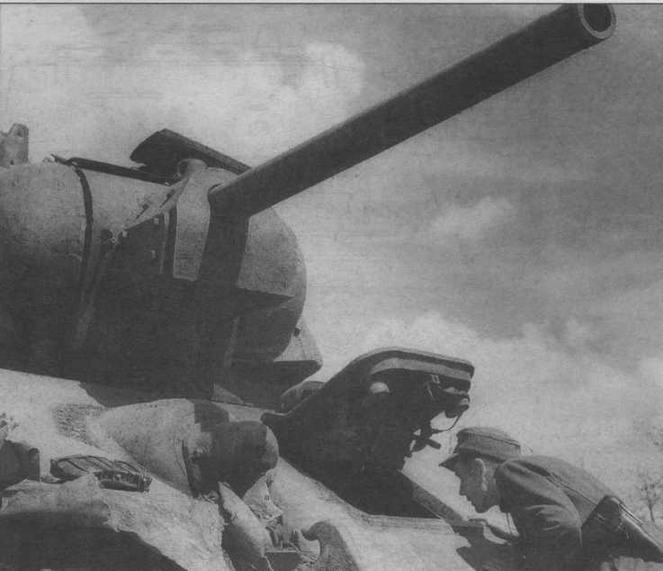 Немецкий солдат осматривает подбитый советский огнеметный танк ТО-34. Курская дуга, 1943 год