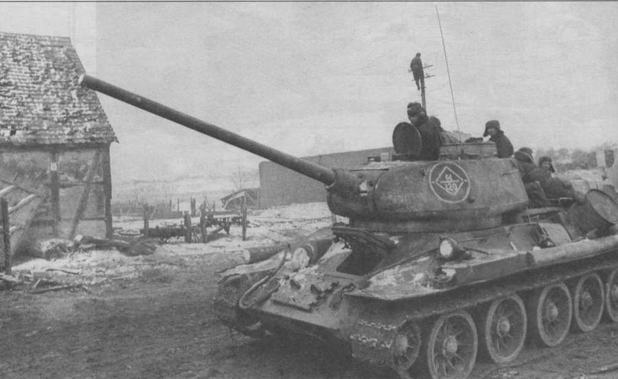 Советские танки проходят через немецкий город Рец, 1945 год. У этого Т-34-85 выпуска 1944 г. в ходовой части используются литые опорные катки. Тип бандажа определить трудно, так как даже если в нем есть вентиляционные отверстия, то они полностью забиты грязью