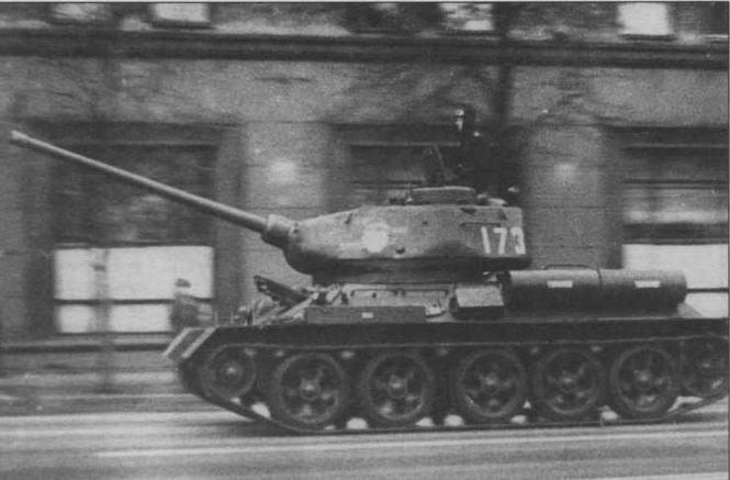Т-34-85, прошедший заключительный этап модернизации в 60-е годы. Хорошо видны новые опорные катки, форма антенного ввода радиостанции P-123, а также второй наружный топливный бак и ящик для индивидуального заправочного насоса на левом борту корпуса. Москва, 9 мая 1985 года