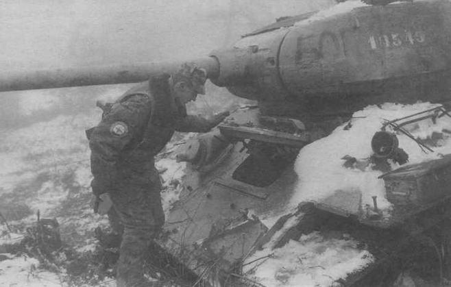 Военнослужащий Российской Армии из состава международных сил по поддержанию мира в Боснии осматривает подбитый сербский танк Т-34-85. Босния, 1996 год