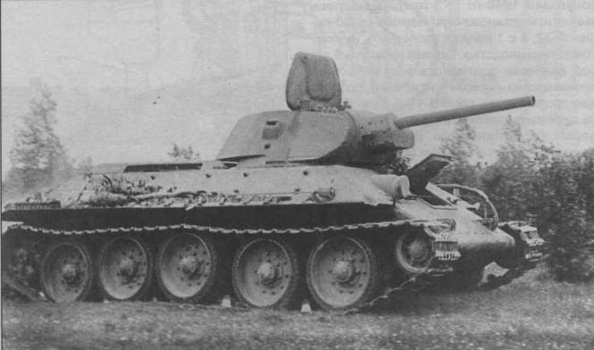 Танк Т-34 выпуска 1941 года. Хорошо видны антенна, уложенная по-походному, и бочки для крепления наружных топливных баков на борту корпуса