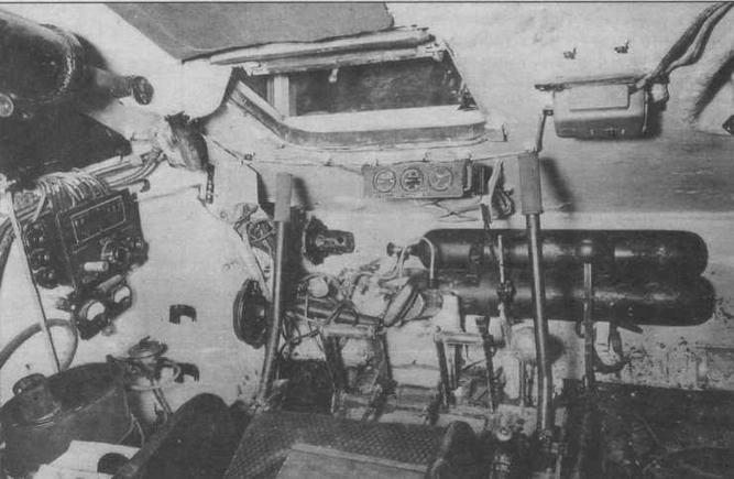 Отделение управления танка Т-34. Место механика-водителя. Черный цилиндр слева вверху— уравновешивающий механизм крышки люка. Справа от люка, над баллонами со сжатым воздухом — аппарат ТПУ