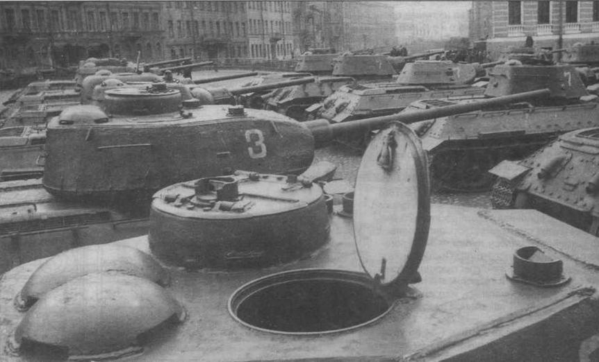 Танки Т-34 и Т-34-85 перед парадом в Ленинграде, 1945 год. На переднем плане башня танка 1944 года выпуска с двухстворчатой крышкой люка командирской башенки, приборами наблюдения МК-4 без броневых крышек и пушкой С-53. Вторая машина в этом ряду — выпуска 1945 года