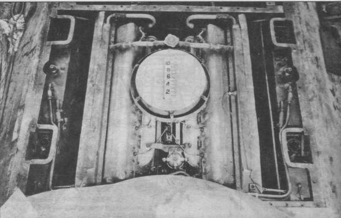 """Вид на двигатель танка Т-34 а стороны башни. За """"блином"""" воздухоочистителя виден заливной тройник с паровоздушным клапаном, предназначенный для заливки воды в систему охлаждения По бортам, между шахтами под вески видны масляные баки"""