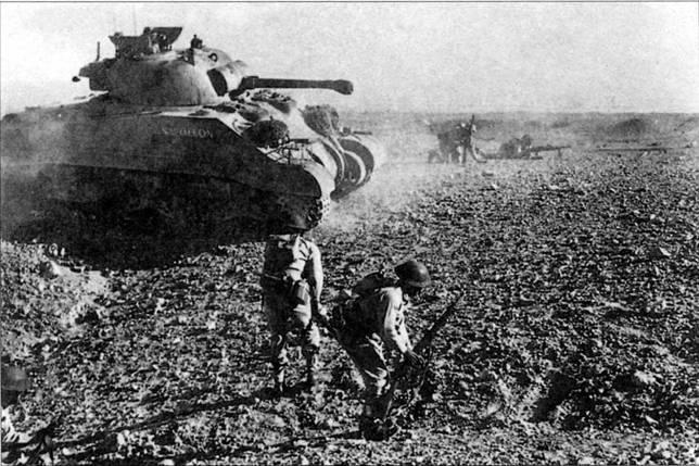 Танк М4 под названием «Наполеон» (обратите внимание на тележки подвески) поддерживает атаку британской пехоты в Северной Африке в конце октября 1942 г. «Шерманы» находились в авангарде британских войск, сражавшихся против армий стран Оси.