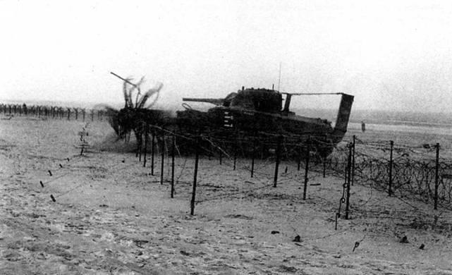 В ходе учебной высадки танк с бойковым тралом «Шерман-Краб I» проделывает проход в проволочных заграждениях. Обратите внимание на насадки на выхлопе и на воздухозаборнике, а также на шкалу глубин, нарисованную на корпусе. Преодолев заграждение, машина функционировала как обычный танк.
