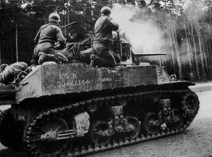 Экипаж танка М5А1 3-й танковой дивизии ведет огонь по немецким снайперам в окрестностях г.Дессау. Германия, апрель 1945 года