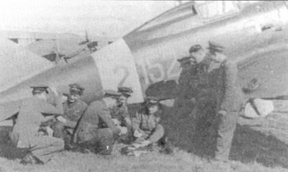 Летчики 2-й группы расслабляются с игрой в карты в тени фюзеляжа истребителя Режжиане Re. 2001. Группа интенсивно действовала с сицилийских аэродромов в период весеннего 1942г. воздушного наступления ни Мальту. В тот период наиболее отличились следующие летчики: тененте Джорджио Почек (пять побед), сототененте Карло Сеганти (пять побед), сототененте Агостино Челентано (семь побед), марисчиалло Олиндо Симонато (пять побед) и серженте мажжиори Чезаре Ди Берт (шесть побед).