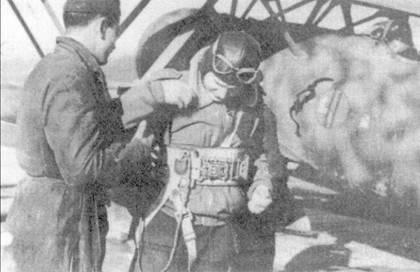 Механик помогает летчику 160-й группы одеть парашют, Греция, конец 1940г. Все три эскадрильи группы (393-я, 394-я и 395-я) в течение всей греческой кампании базировались па албанских аэродромах. Лучшими пилотами группы являлись капитане Эбер Гиудиче, тененте Джулиано Физзоре и серженте Манфредо Бианчи. Обратите внимание — на борту истребителя изображен профиль дуче.