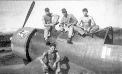 Механики позируют на самолете «GUS'S GOPHER». На капоте двигателя изображен персонаж диснеевского мультфильма, на борту фюзеляжа ниже кабины — восемь отметок о победах в воздушных боях. На Соломонах в составе эскадрильи VMF-2I3 Томас одержал 16,5 побед, еще два «Зеро» он сбил 16 февраля 1945г.