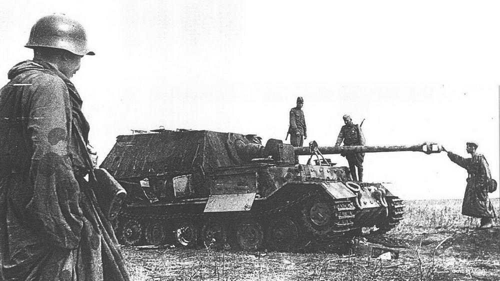 """Разведчики 13-й армии рассматривают подбитый """"Фердинанд"""". Машина имеет пробоину в левом борту у тормозного барабана. 17-20 июля 1943 г."""