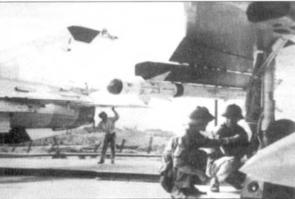 Техники по вооружению проверяют подвешенную под крыло истребителя МиГ- 21 ПФМ ракету К-13. На заднем плане — техник осматривает сопло двигателя истребителя МиГ-2 /МФ.