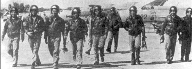 Группа пилотов 921-го ИАП сфотографирована па аэродроме Нойбай после учебного группового полета, на заднем плане — линейка истребителей Миг-21 ПФМ.