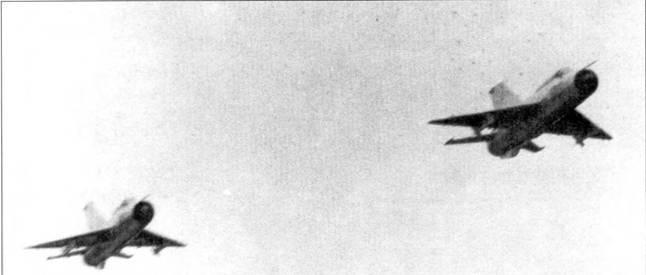 Два истребителя МиГ-21 ПФМ взлетели в аэродрома Нойбай, середина мая 1972г. Этот период был отмечен интенсивными воздушными боями между американскими и вьетнамскими самолетами. Оба самолета вооружены ракетами К-13. Обратите внимание на отсутствие на центральных подфюзеляжных узлах подвески дополнительных топливных баков, видимо самолетам предстоит бой непосредственно в воздушном пространстве аэродрома.