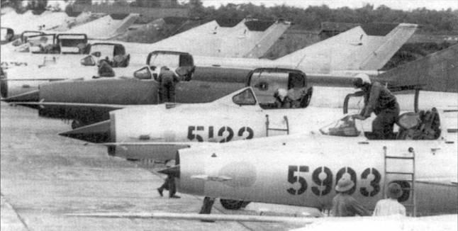 Истребители МиГ-21 из 927-го ИАП, аэродром Нойбай, лето 1972г. В одной линейке стоят истребители МиГ-21ПФМ и МиГ-21МФ, двухместные МиГ-21УМ. Обратите внимание на самолет без бортового номера (третий справа)— он целиком окрашен в зеленый цвет.
