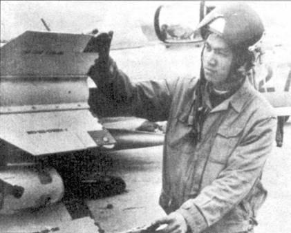 Нгуен Тиен Сам (шесть побед) проверяет роллероны на ракете К-13, подвешенной под плоскостью крыла истребителя, на котором ему предстоит совершить боевой вылет. «Советский Сайдуиндер» — ракета К-13 — оставалась основным оружием истребителей МиГ-21 на протяжении всей войны во Вьетнаме.