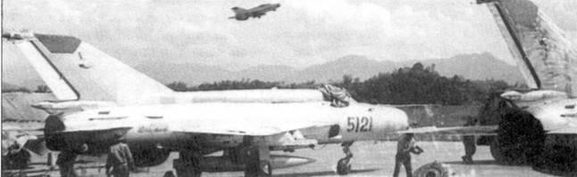 Осень 1972г. В учебный полет уходит двухместный МиГ-21УМ. На земле техники готовят к взлету истребитель МиГ-21МФ. На самолете с бортовым номером «5121» будущий Герой Советского Союза летчик-космонавт СССР (и Вьетнама) Фам Туан сбил в ночь на 27 декабря 1972г. стратегический бомбардировщик B-52D.