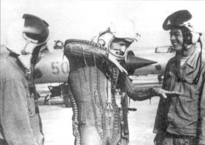 Фам Туан (в центре) жестами показывает как он атаковал стратегический бомбардировщик. Справа от Туана стоит известный ас Нгуен Дак Соат (он посмеивается). В 70-е годы летчики МиГов редко летали в высотно-компенсирующих костюмах, поскольку воздушные бои велись на сравнительно небольшой высоте. На Фам Тане одет ВКК, так как перехват В-52 приходилось осуществлять в стратосфере. Соат и его неустановленный коллега одеты в обычные летние летные курки.