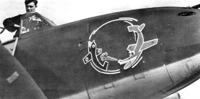 Крупный план эмблемы «Der Ringelpitz» 1-го стаффели 26-й эскадры «Хосрт Вессель». Обведенный белой окантовкой красный германский аллигатор пытается достать черно-белую британскую рыбину. Пасти обоих живностей прорисованы красным цветом.