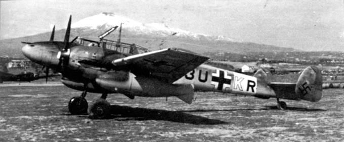 Bf. 110D-3 из 7./ZG-26 с подвешенными под крылом баками емкостью 198 галлонов на аэродроме Сицилия в ожидании вылета на сопровождение в Африку транспортных Ju-52. Хорошо видна белая буква «X» на капоте двигателя – стоит мотор DВ-601X, который работал на бензине СЗ с октановым числом 93.