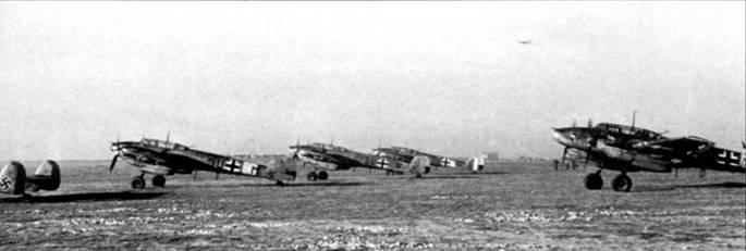 За эмблему II/ZG-26 прозвали «Clog Gruppe». Эта группа принимала участие в операции «Барбаросса» с первых часов. На носах фюзеляжей самолетов избражены эмблемы гешвадера, па капотах моторов – эмблемы группы.