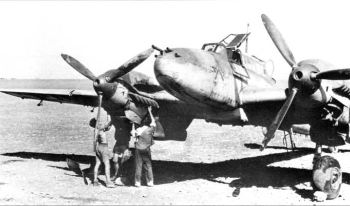 Истребитель-бомбардировщик Bf. 110F-1 с парой подфюзеляжных бомбодержателей ЕТС-500, па которые подвешивались две фугасных юомбы SC-500, две осколочных бомбы SD-250 или контейнеры А В-500 с осколочными и зажигательными бомбами. Судя по характеру местности, снимок сделан в Северной Африке.