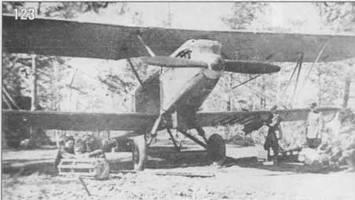 123. На замаскированный в лесу Р-5 подвешивают бомбы.