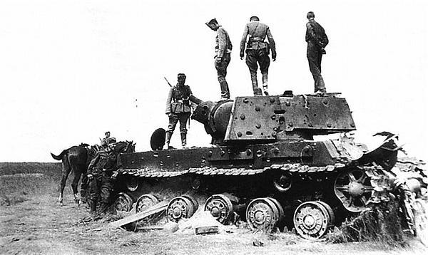 Немецкие солдаты осматривают подбитый танк КВ-1. Район Красногвардейска, 1941 год. Танк попал под сильный артиллерийский огонь — он имеет следы многочисленных снарядных попаданий, орудие сорвано с противооткатных устройств.
