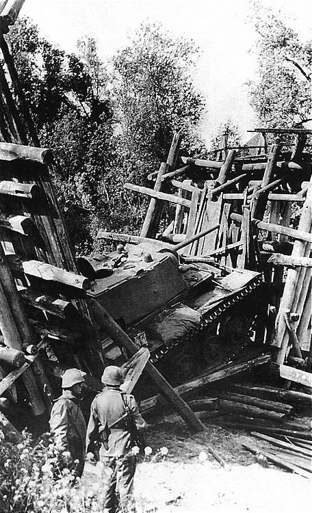 Этот снимок хорошо демонстрирует проблемы, возникающие из-за высокой массы танков КВ-1 при их эксплуатации: немецкие солдаты осматривают танк (с литой башней), провалившийся при движении по мосту. Лето 1942 года.